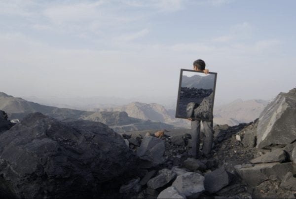 Man holding mirror on mountain