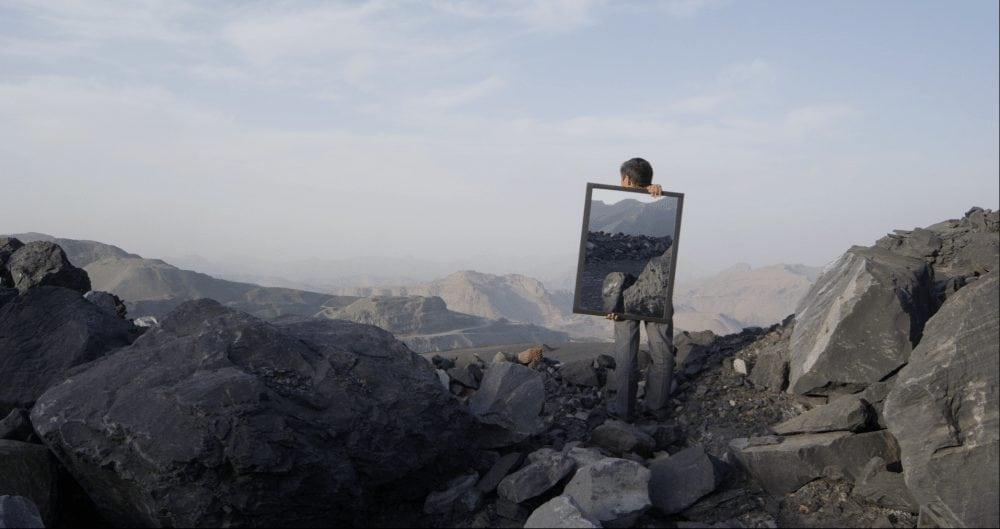 Man holding mirror on mountain