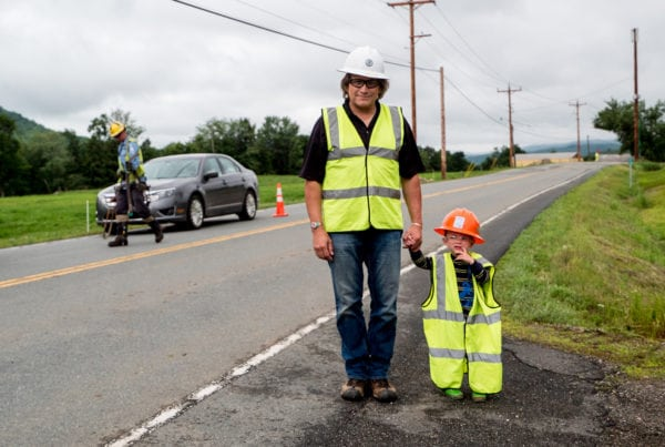 Man and child in vests on side of road